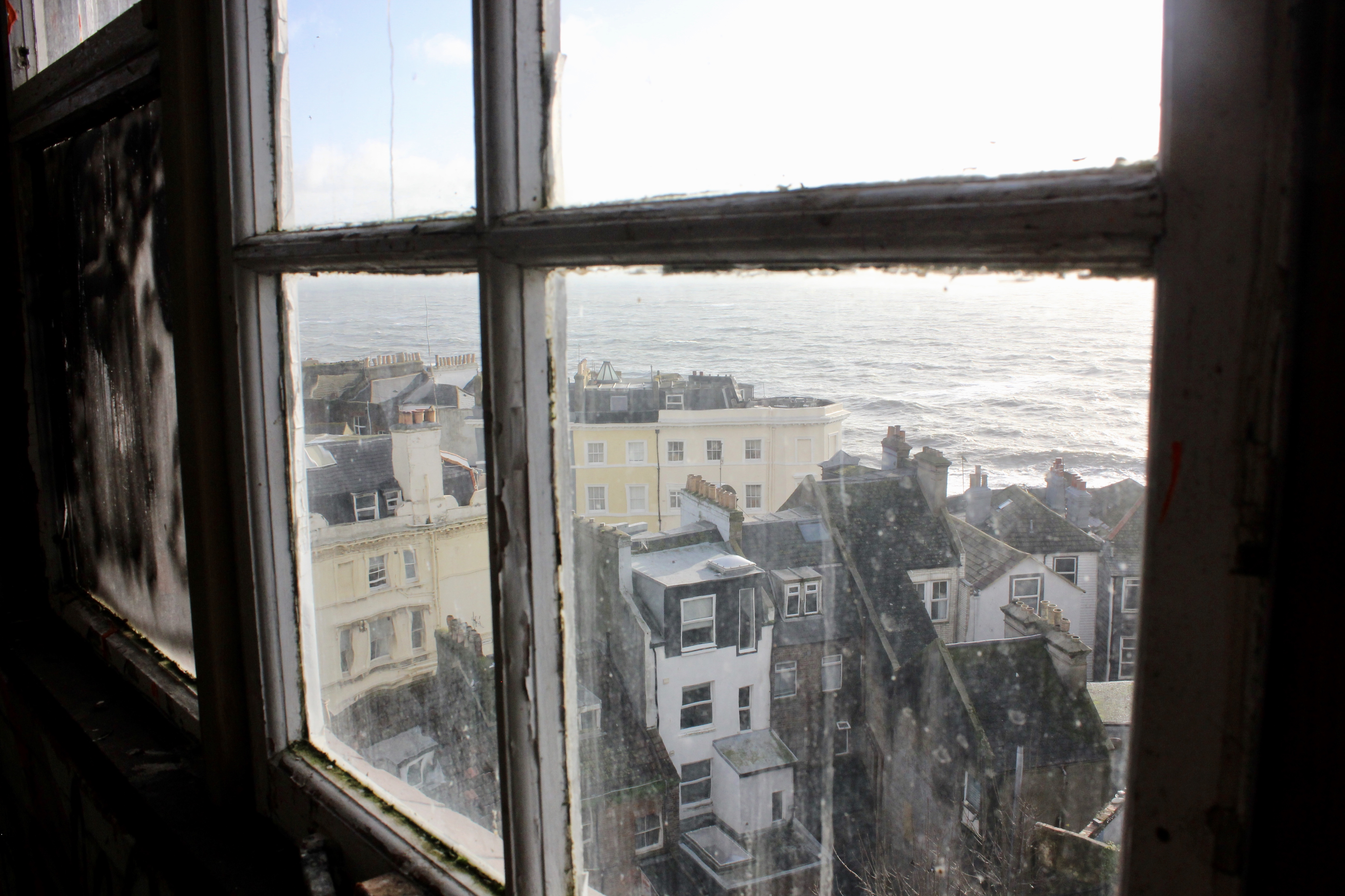 Looking out of a window at Hastings, the sea in the distance