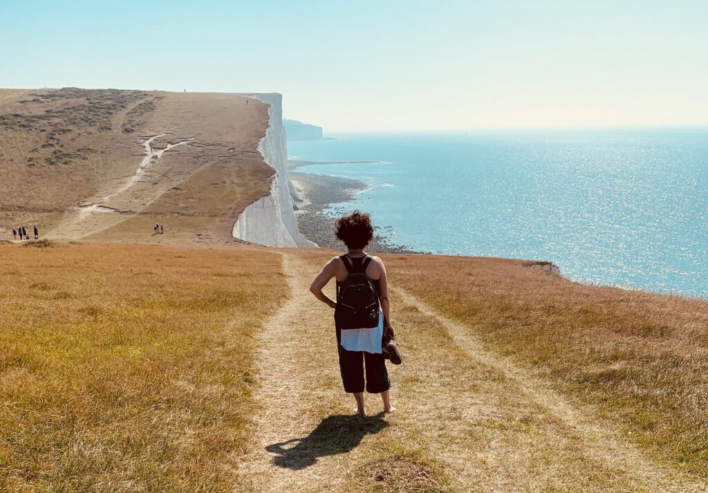 The writer Alinah Azadeh stands on the cliffside path approaching Birling Gap. The grass is yellow from summer. The sea is blue. A few people are in the far-off distance.